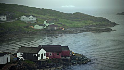 St. Anthony, Newfoundland, is located in the far northwestern corner of Newfoundland. It's a remote fishing hub and service center for western Newfoundland and southern Labrador. An iceberg, seen at the top of the photo, floats outside the entrance to the harbor.