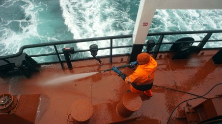 Gudmoder Halldorsson hoses down the deck of the Bruarfoss as it sails from Newfoundland to Iceland.