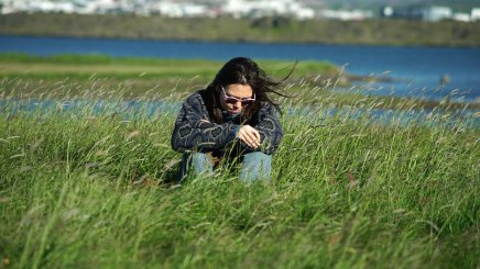 Ihila sits on the grass near the president's house outside Reykjajvik.
